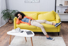 Bored African American Woman Chilling On Yellow Couch