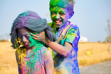 Young Kid From The Back Applying Holi Colors To Girls Face During Holi Festival Celebration - Concept Of Kids Having Fun By Playing Holi During Festive.
