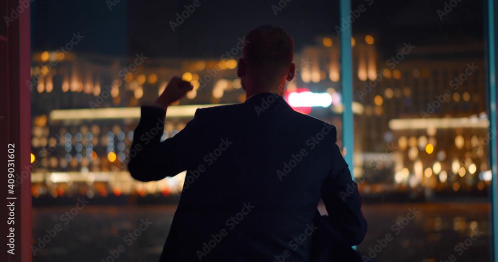 Fototapeta Back view of businessman celebrating success standing near panoramic window with night cityscape
