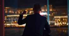 Back View Of Businessman Celebrating Success Standing Near Panoramic Window With Night Cityscape