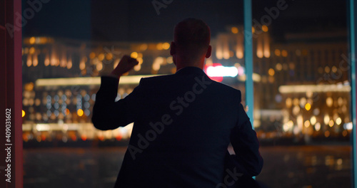 Slika na platnu Back view of businessman celebrating success standing near panoramic window with