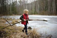 Little Boy Playing Large Branch On Shore Of Forest Lake On Early Spring Day. Surface Of Lake Is Still Under Ice. Child Tries To Break Ice With Stick.