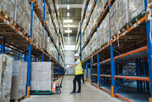 Caucasian Man Moving Boxes In A Huge Warehouse