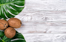 Green Leaves Monstera With Coconuts On White Wooden Background Top View. Copyspace For Your Text, Banner