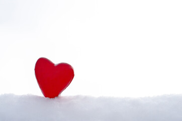 Beautiful red heart in the snow on a light background. Valentines day concept