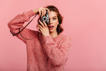 Surprised Girl In Knitted Sweater Taking Photos. Studio Shot Of Female Photographer Holding Camera On Pink Background.