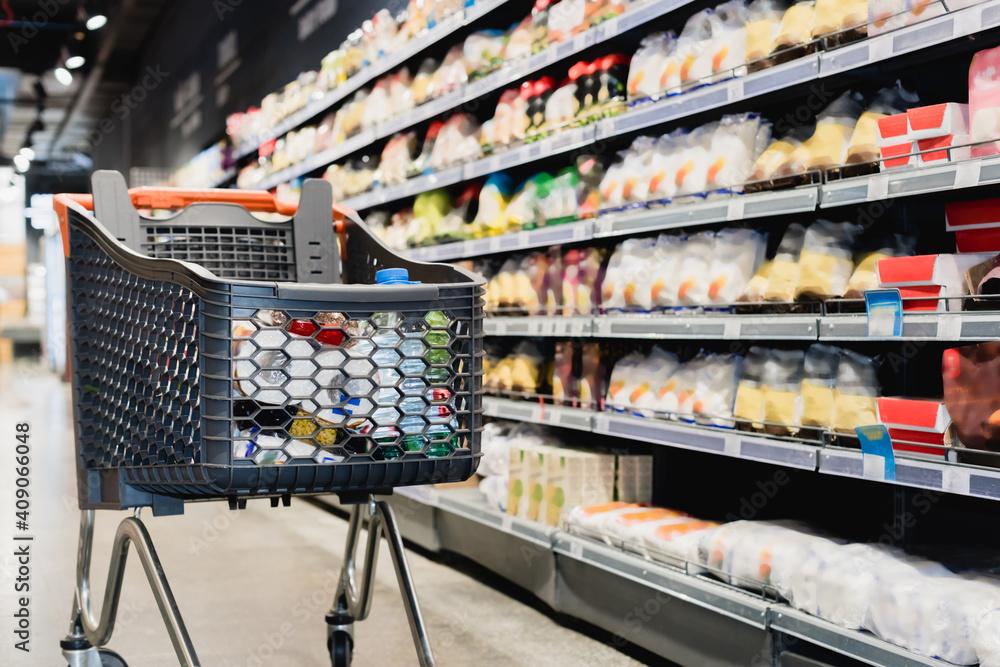 Fototapeta Shopping cart near packages on shelves in supermarket