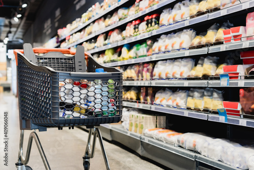 Slika na platnu Shopping cart near packages on shelves in supermarket