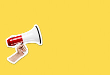 Hand Holding Megaphone On Bright Yellow Background With Plenty Of Copy Space. Magazine Collage Cut Out Style
