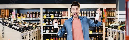 Obraz Excited man holding bottles of wine in supermarket, banner - fototapety do salonu