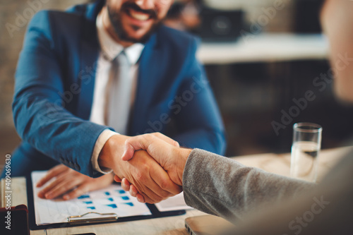 Close up of business handshake in the office. Selective focus on hands