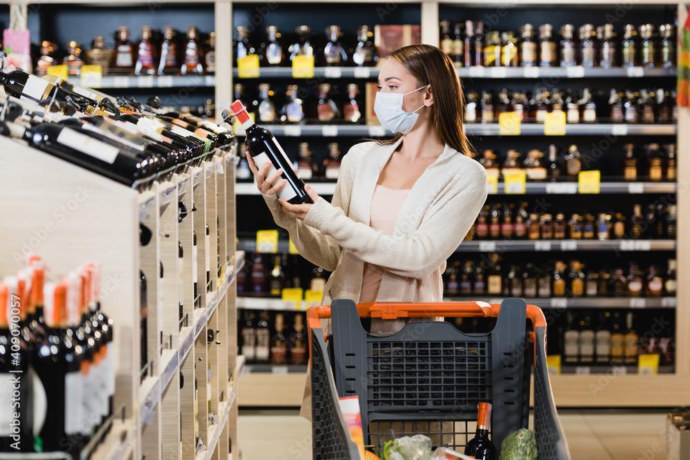 Fototapeta Woman in medical mask holding wine bottle near shopping cart in supermarket