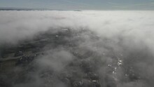 Wide Angle Drone Footage Through The Cloud Line On A Bright Sunny Morning Over Folsom, USA With Scattered Fog And Mountains In The Background