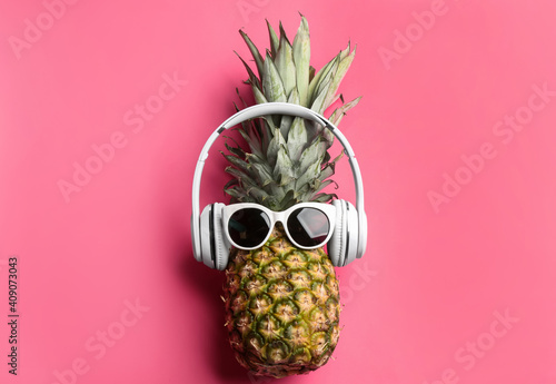 Pineapple with sunglasses and headphones on pink background, top view. Creative concept