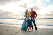 Barefoot Happy Young Family On Beach With Mom In Long Dress