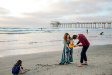Girl Plays In Sand As Parents Check Baby Brother At Beach Near Pier