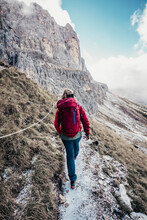 Young Female Mountaineer Hikes Towards Rock Face In Italian Dolomites
