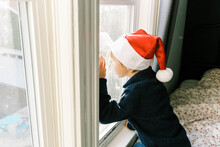Little Boy With Christmas Hat Looking Out The Window For Santa Clause