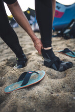 A Woman Swaps Her Flip Flops For Neoprene Booties Before Kiteboarding