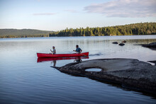 Paddlers Steer Canoe Past Rocky Point In Wilderness Lake In Maine