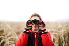 Woman Holding Binoculars At Farm