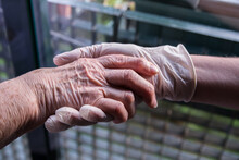 50-year-old Woman And 85-year-old Mother Holding Hands. COVID-19