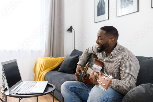 Obraz Smiling young African American male musician playing guitar during an online concert at home while isolated during coronavirus, sitting on the sofa, using a laptop to stream record or teach music - fototapety do salonu