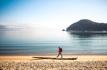 Woman Walking Down Sandy Beach With Backack With Ocean Behind Her