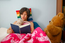 A Boy Lays In Bed With Colorful Blankets Reading With Teddy Bears
