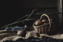 Dark Brown Eggs In Basket On Burlap With Background Branch