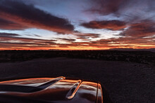 Vibrant Desert Sunrise Reflected On Hood Of Parked Vehicle