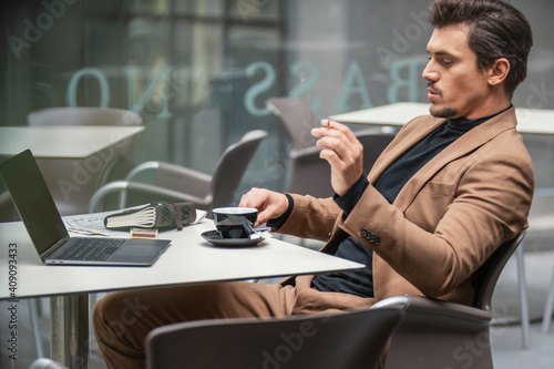 Canvas Print a man in a suit smokes at the table