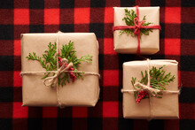 Rustic Christmas Gifts On Red Checkered Surface