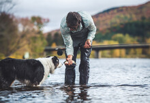 Man Holding A Small Trout While Dog Sniffs Fish