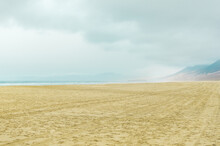 Infinite Beach With Mountains In The Background On Hazy And Cloudy Day. Cofete Beach, Canary Islands.