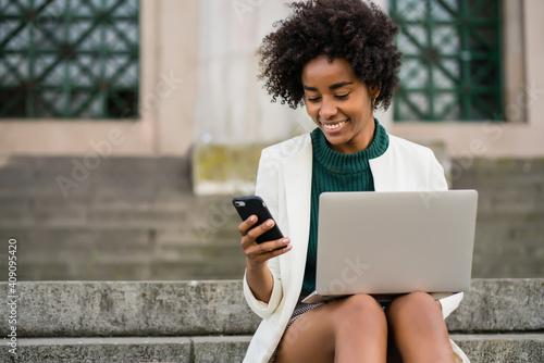 Business woman using her mobile phone and laptop outdoors.