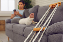 Close-up Of Metal Crutches For Walking And Young Woman With Broken Leg In Cast With Phone On Sofa At Home, Selective Focus. Trauma, Injury, Recovery, Rehabilitation Concept