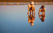 Two Fantastically Beautiful Girls In Unusual Outfits On A Beautiful Transparent Salt Lake Are Looking For Something In A Shiny Surface