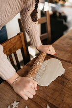 Young Woman Rolling Out Clay To Create Christmas Ornaments