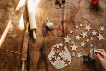 Hand Of Young Woman Creating Christmas Star Ornaments With Clay