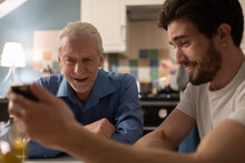 Young Man Showing Funny Photos To Father