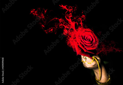 Fotografía Female hand holding a brig red rose with fire and smoke isolated on dark backgro