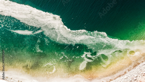 Obraz na plátně Aerial shot of a seascape with big waves and green wa
