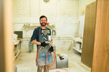 Smiling Male Worker Using A Spray Gun To Paint A Wooden Door