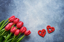 Valentine's Day Greeting Card. Bouquet Of Red Tulips And Two Red Hearts On A Blue Background