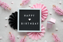Text Happy Birthday On Text Board, Letterboard. Creative Flat Lay In Pink And Black On Cream White Textile. Party Decor, Paper Fans, Hearts And Gift Box. Lights On Pretty Decorative Garland.