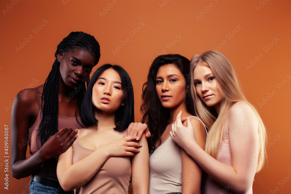 Fototapeta SaveDownload Previewyoung pretty asian, caucasian, afro woman posing cheerful together on brown background, lifestyle diverse nationality people concept