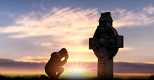 A Man Is Praying To God's Cross In The Sunset.