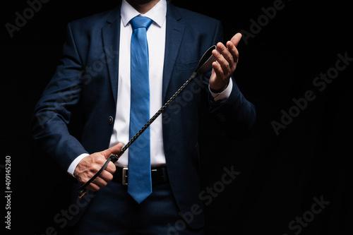 Fotografia, Obraz male dominant holds a leather whip Flogger for hard BDSM sex