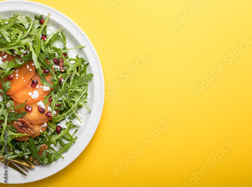 Obraz Persimmon salad with arugula, nuts, goat cheese, pomegranate. Healthy vegetarian food salad concept. - fototapety do salonu